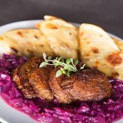 Duck style roasted seitan with braised red cabbage and potato pancakes